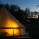 Canvas glamping tent glows at night
