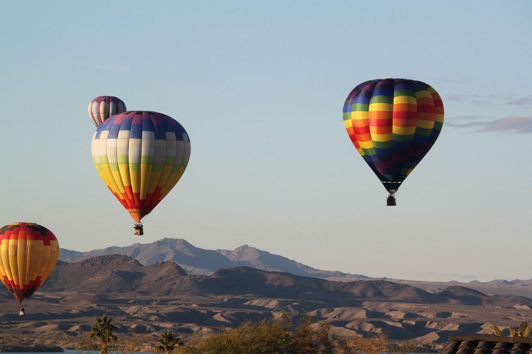 Hot air balloons floating over the desert