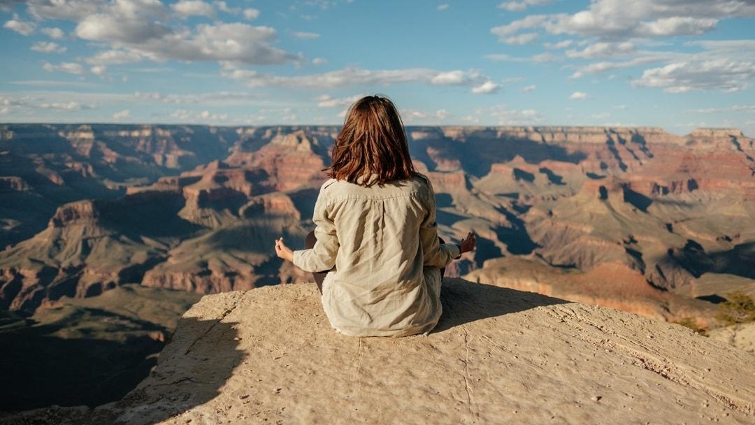 Woman meditating on the rim of the Grand Canyon, Arizona