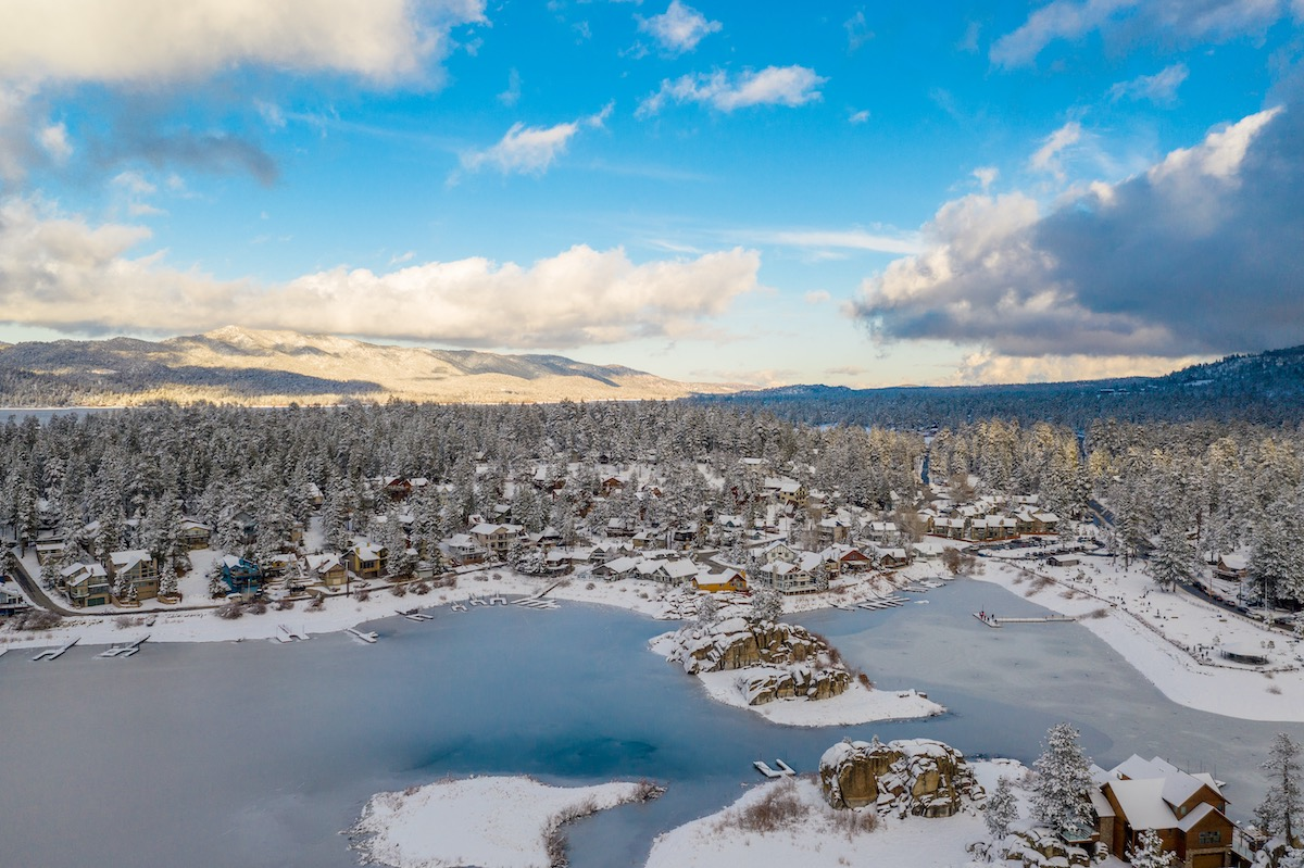 Aerial view of Big Bear Lake and town in California with the lake frozen on a sunny blue sky day in the Winter with pine trees below.