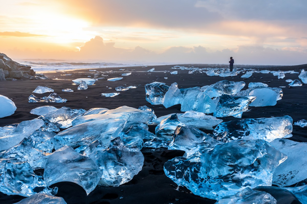 Diamond Beach in Iceland with blue icebergs melting on the black sand and ice glistening with sunrise sun light, tourist looking at beautiful arctic nature scenery, Icelandic South coast, Jokulsarlon