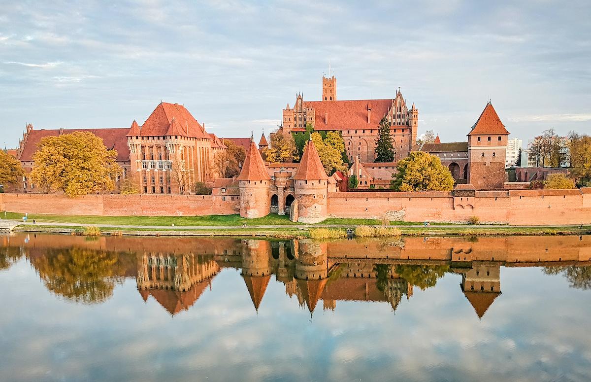 Malbork castle autumn panorama with reflection, at sunset